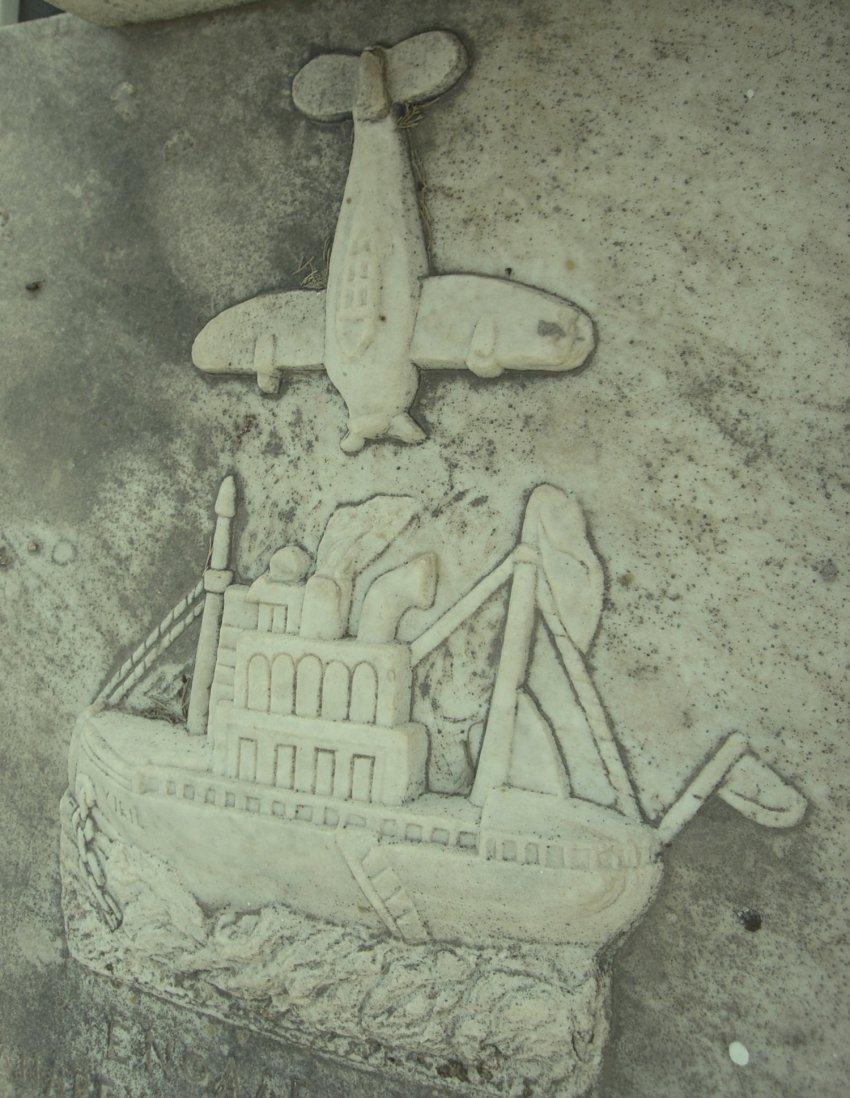 Η ανάγλυφη απεικόνιση του βομβαρδισμού του WIRIL στην επιτύμβια πλάκα.