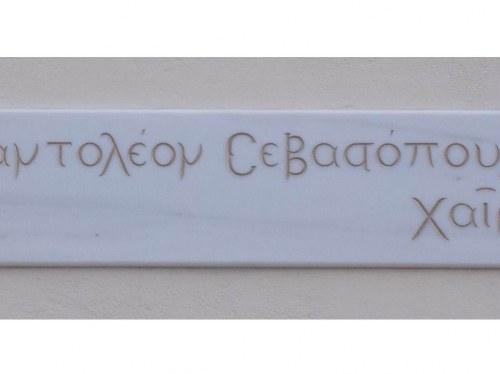 Η επιγραφή που εντοιχίστηκε το 2019 στις εγκαταστάσεις του Εκπαιδευτηρίου στη Νέα Σμύρνη.